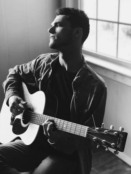 guitarrista sentado de perfil mirando al infinito. Fondo blanco y negro